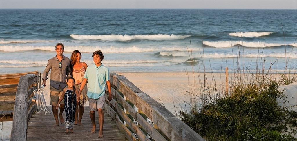 Family walking on boardwalk in New Smyrna Beach